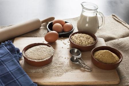 avena en hojuelas: Ingredientes para el pan, la harina de grano entero saludable de trigo integral, avena y germen de trigo con leche y huevos Foto de archivo