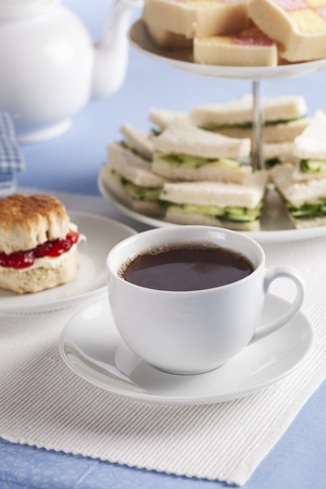 english cucumber: Afternoon cup of tea with cucumber sandwiches and scones in the background. Stock Photo