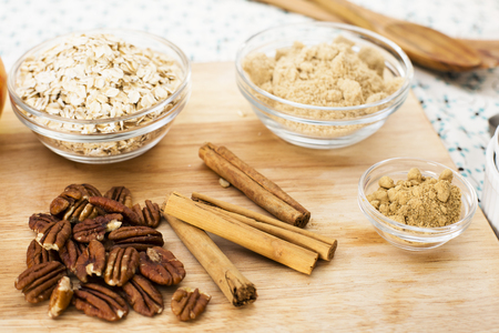 apple crumble: Ingredients for apple crumble, pecans, cinnamon sticks, sugar, spices and oats.