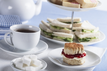 Cup of tea with sugar cubes and scones, cucumber sandwiches in the background