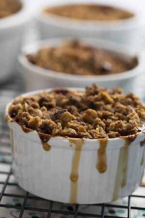 apple crumble: Personal sized apple crumble with filling dripping down the sides. Stock Photo