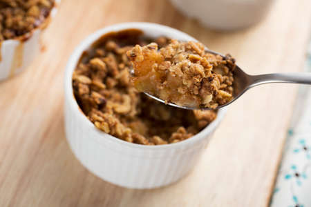 apple crumble: Spoon full of fresh apple crumble from single serving
