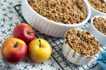 apple crumble: Freshly made apple crumble on cooling rack with apples