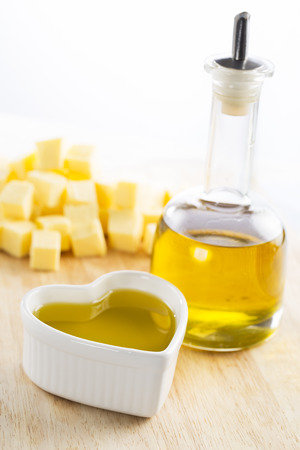 Olive oil in bottle and in a heart with butter in the background Stock Photo