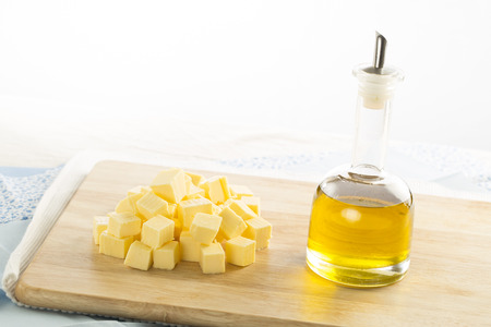 Olive oil in bottle and butter cubes on food preparation surface