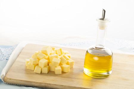 Olivenöl in Flasche und Butter Würfel auf Lebensmittelzubereitung Oberfläche Standard-Bild - 25278506