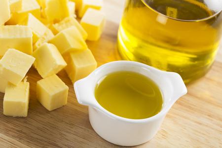 mantequilla: Aceite de oliva en pequeño recipiente de vidrio con la botella de aceite y cubos de mantequilla