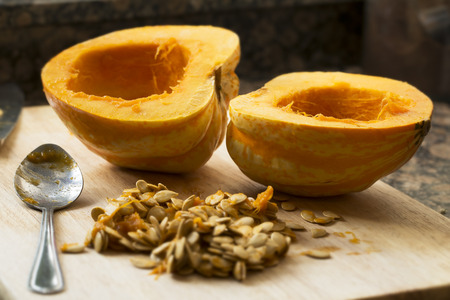 Winter squash cut in half with spoon and seeds scooped out
