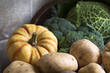Basket of winter vegetables including broccoli, sweet lightning squash and potatoes  Stock Photo