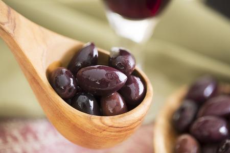 kalamata: Wooden scoop of kalamata olives.