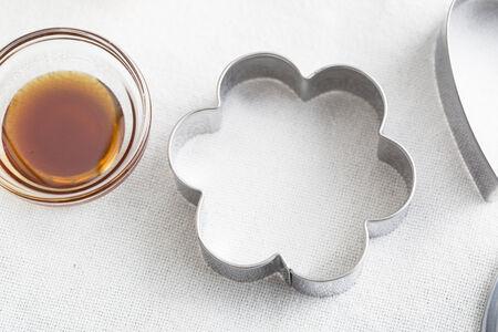 꽃 모양의 쿠키 커터와 바닐라 추출물의 작은 유리 그릇