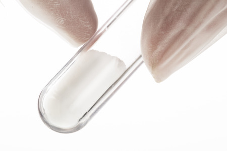pharmacy equipment: Close up of white powder in test tube being held by fingers