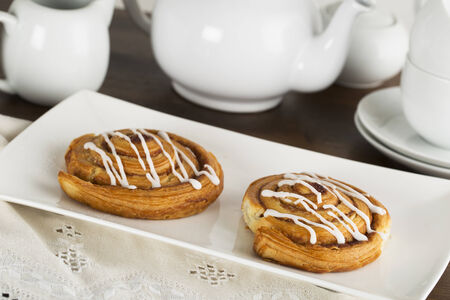Two tempting cinnamon rolls with tea pot in background photo