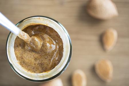 Almond Butter in pot met lepel, van direct boven Stockfoto