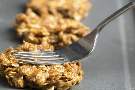 oatmeal cookie: Fork pressing down raw oatmeal cookie dough on baking sheet