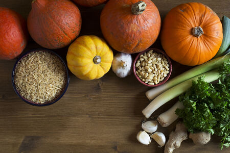 Brown rice, various types of winter squash, leeks , pine nuts and garlic from above with copy space, a healthy eating still life