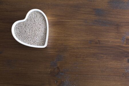 hispanica: White Chia seeds in heart shaped container on table with copy space Stock Photo