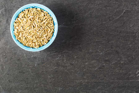 fennel seeds: Bowl of fennel seeds on stone surface with copy space.