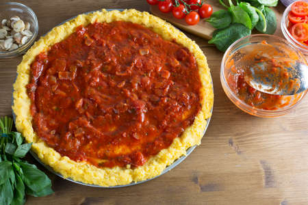 pizza crust: Baking polenta pizza, pizza crust with tomato sauce and empty tomato sauce bowl with spoon on the right side, other ingredients surrounding pizza.