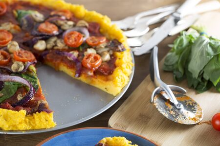 Vegan polenta pizza with cherry tomatoes, mushrooms, spinach and onions with slice removed and pizza slicer to the side.