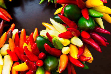 string top: String of colorful peppers on a wooden table top.