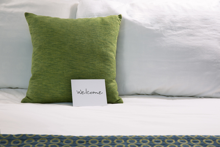 concept hotel: Welcoming hotel bed with pillows and welcome card close up. Stock Photo