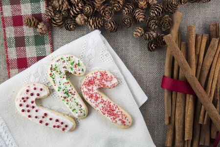 pine three: Three frosted and decorated candy cane shaped sugar cookies on a cloth napkin with cinnamon sticks and pine cones