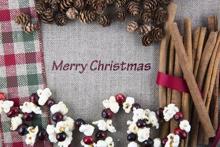 palomitas: La tela de lino impresa con Feliz Navidad rodeado de ramas de canela, guirnaldas de palomitas de maíz y piñas.