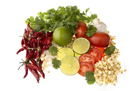 hot peppers: Limes, tomatoes, cilantro hot peppers and garlic, all possible ingredients for a posole. Stock Photo