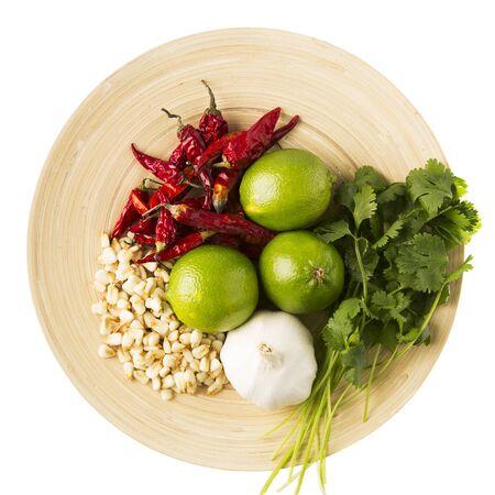 chiles picantes: Secado sémola de maíz, ajo, limón, cilantro y chiles: ingredientes para una versión de un pozole. En la placa de madera y aislado en un fondo blanco. Foto de archivo