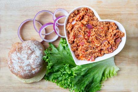 sloppy: Heart healthy vegan sloppy joe sauce made with quinoa, with a bun, lettuce and onion.