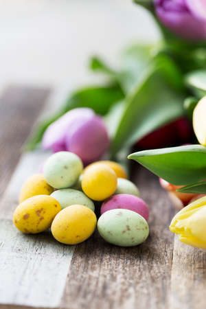 vertical orientation: Close up of milk chocolate eggs on table with flowers vertical orientation. Stock Photo