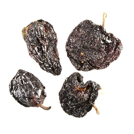 Four dried poblano chilies isolated on white.