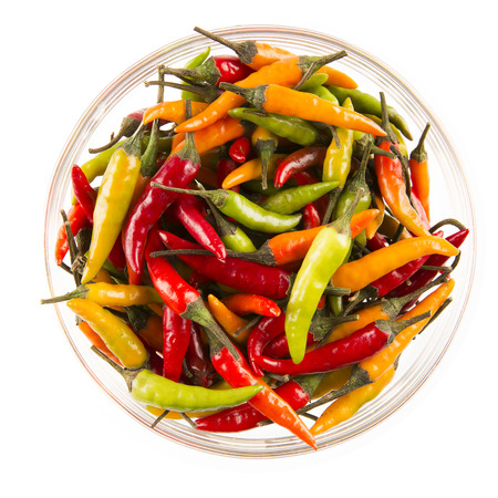 Bowl of yellow, red and green hot chili peppers isolated on white.  View from above.