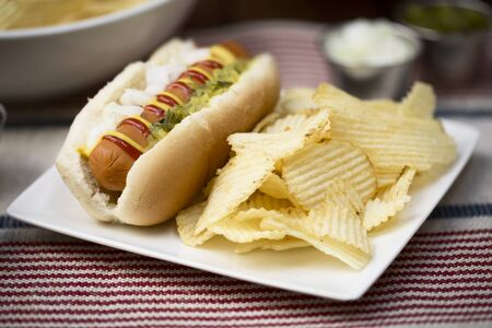 crisps: Veggie hot dog topped with mustard, ketchup, onions and relish, served with potato crisps (chips).
