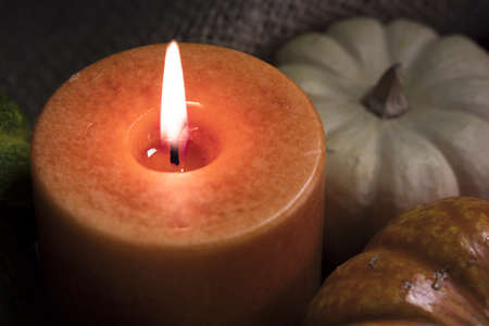 candlelit: Fall theme close up of orange candle burning with gourds