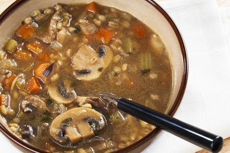 Bol de champignons maison et soupe à l'orge avec une cuillère en elle prête à manger