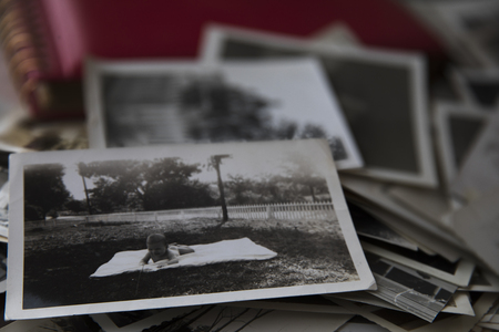 Stack of old photos with photo of baby on the top. 版權商用圖片