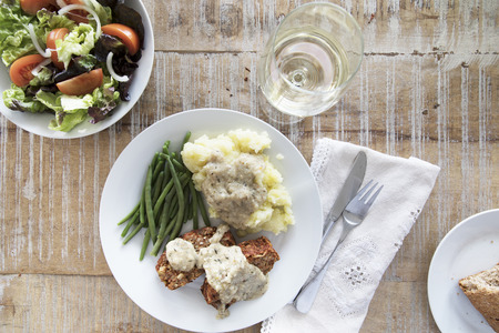 Slices of vegan lentil loaf covered in gravy with mashed potatoes and green beans, flat lay.