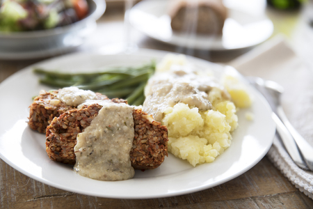 Slices of vegan lentil loaf covered in gravy with mashed potatoes and green beans.