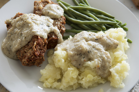 Mashed potatoes covered in gravy with vegan lentil loaf and green beans close up.