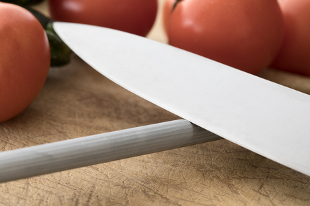 Close up of knife on honing steel with vegetables in background Stock Photo