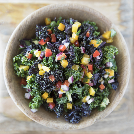 Healthy kale salad with fresh bell peppers and red onions in a wooden bowl viewed from above. 免版税图像