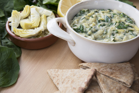 Bowl of vegan spinach artichoke dip with pita and ingredients.