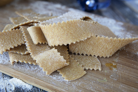 Fresh cut homemade pappardelle pasta on wooden board.