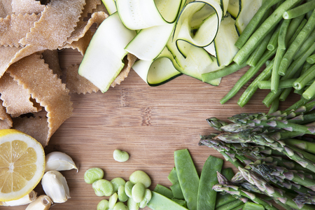 Fresh ingredients for pasta, zucchini, lima beans, green beans, lemon, garlic and homemade whole wheat pappardelle pasta. Flat lay with copy space in center. Archivio Fotografico