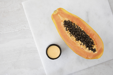 Half a papaya on a marble surface with small jare of papaya extract cream.