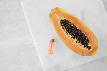 Half a papaya on a marble surface with small bottles of papaya extract. Imagens