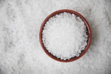 Cristalli di sale in una ciotola su letto di sale, distesi.