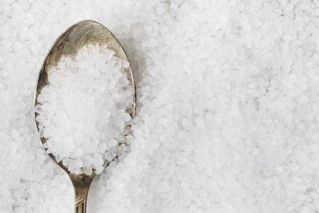Salt crystals in metalspoon on bed of salt. Zdjęcie Seryjne